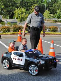 A Police Officer in uniform next to 2 young boys in a toy police car